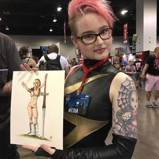 Holding concept art of myself.